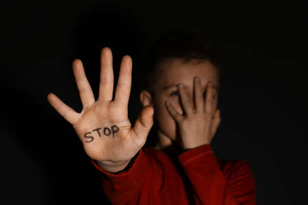 Abused little boy showing palm with word STOP against black background, focus on hand. Domestic violence concept