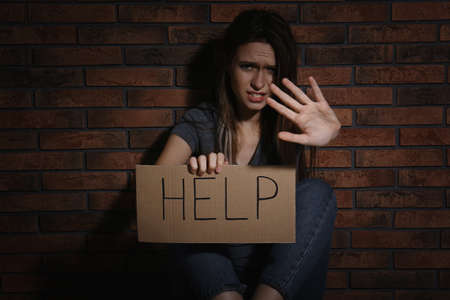 Abused young woman with sign HELP making stop gesture near brick wall. Domestic violence concept 免版税图像