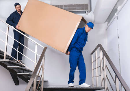 Professional workers carrying refrigerator on stairs indoors