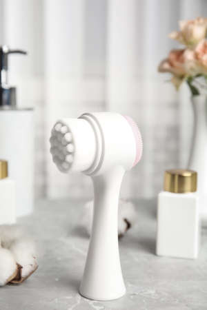 Modern face cleansing brush on light grey marble table. Cosmetic accessory