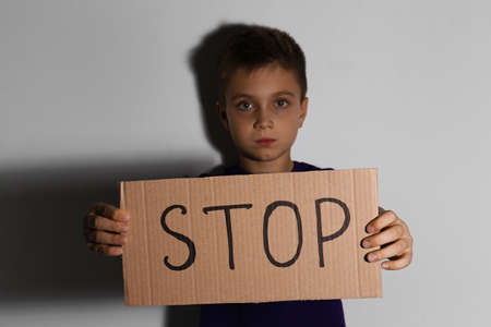 Abused little boy with sign STOP near white wall. Domestic violence concept