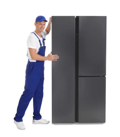 Professional worker carrying refrigerator on white background