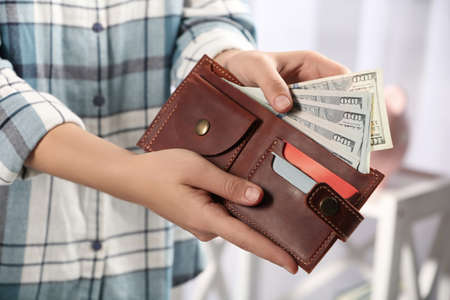 Woman putting money into wallet on blurred background, closeup