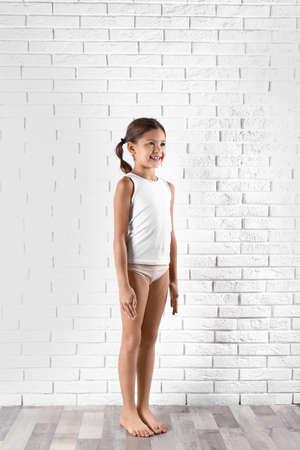 Bambina sveglia in biancheria intima vicino al muro di mattoni bianchi