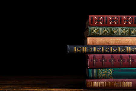 Collection of different books on wooden table against dark background. Space for text