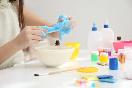 Little girl making DIY slime toy at table, closeup