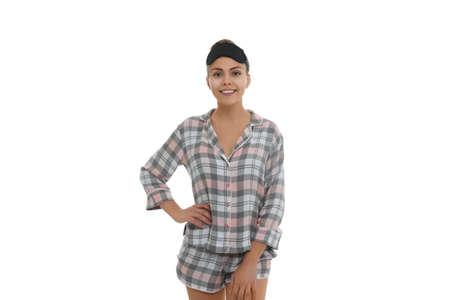 Beautiful woman wearing pajamas and sleeping mask on white background. Bedtime