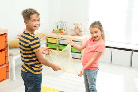 Happy children playing with slime in room