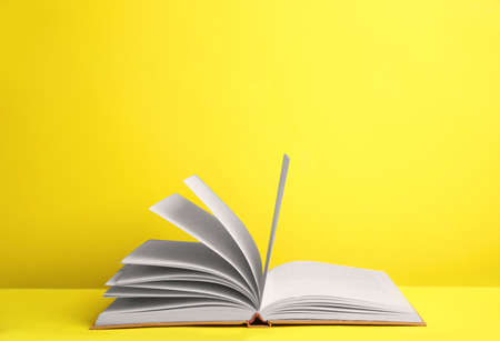 Open old hardcover book on yellow background. Space for text