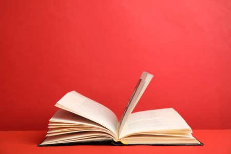 Open oud hardcoverboek op rode achtergrond. Ruimte voor tekst Stockfoto