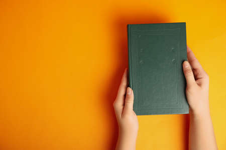 Woman with book on orange background, top view. Space for design