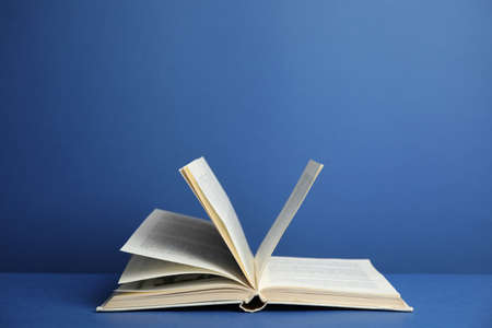 Open old hardcover book on blue background