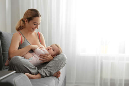 Young woman breastfeeding her baby at home. Space for text