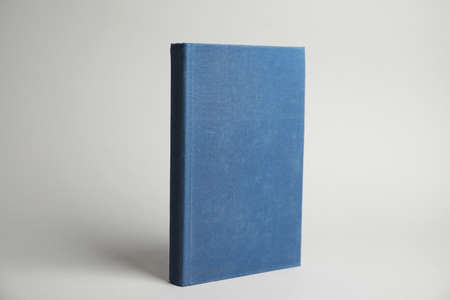 Hardcover book on light grey background. Space for design
