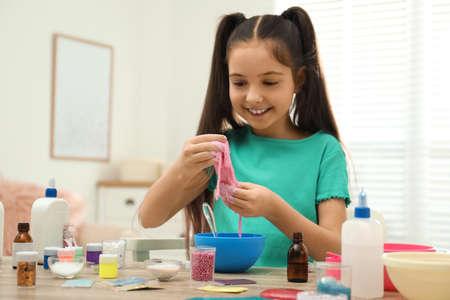 Schattig klein meisje maakt slijmspeelgoed binnenshuis aan tafel