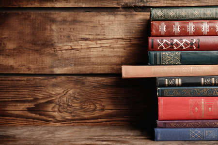Collection of different books on table against wooden background. Space for text