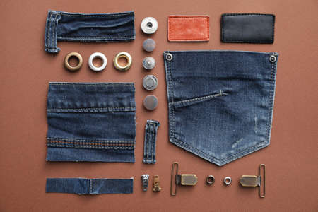 Flat lay composition with garment accessories and cutting details for jeans on brown background