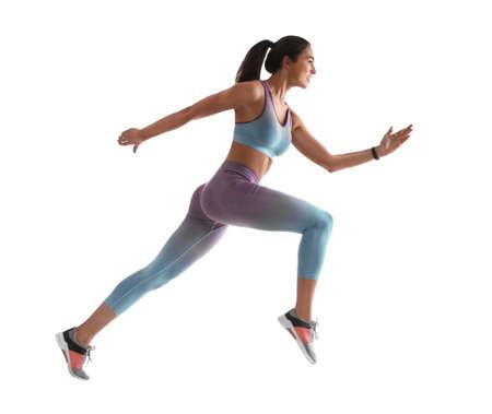 Jeune femme athlétique qui court sur fond blanc, vue latérale
