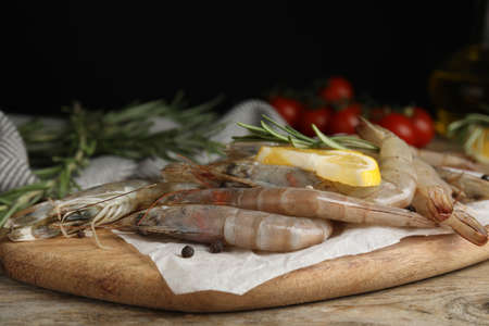 Fresh raw shrimps with lemon slice and rosemary on wooden table Stock Photo