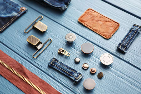 Composition with garment accessories and cutting details for jeans on light blue wooden background