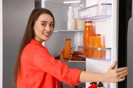 Jonge vrouw die sap uit de koelkast haalt