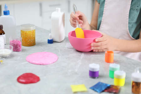 Little girl mixing ingredients with silicone spatula at table, closeup. DIY slime toy