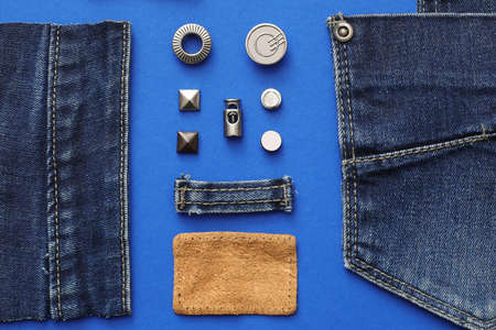 Flat lay composition with garment accessories and cutting details for jeans on blue background Standard-Bild