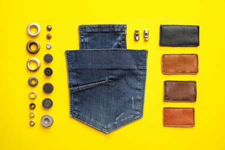Flat lay composition with garment accessories and cutting details for jeans on yellow background
