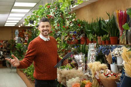 Mannelijke bedrijfseigenaar met klembord in zijn bloemenwinkel