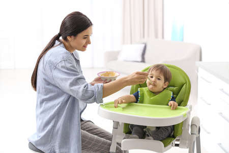 Young nanny feeding cute little baby at home