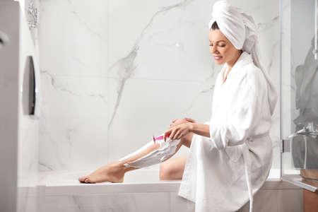 Beautiful young woman shaving legs in bathroom