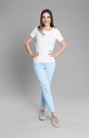 Young woman in stylish jeans on grey background Banque d'images