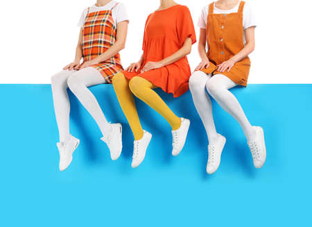 Group of women wearing colorful tights and stylish shoes sitting on color background, closeup