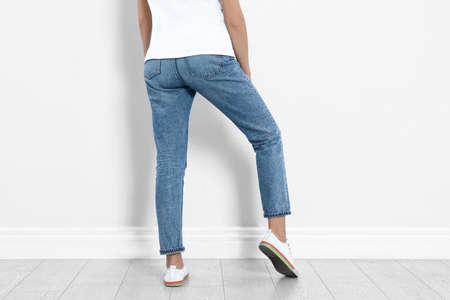 Mujer joven en jeans con estilo cerca de pared de luz, primer plano Foto de archivo