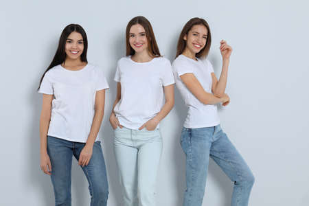Group of young women in stylish jeans on light background