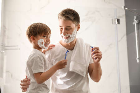 Dad and son with shaving foam on their faces having fun in bathroom