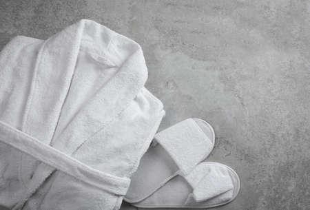 Sauber gefalteter Bademantel und Hausschuhe auf grauem Steinhintergrund, flach Standard-Bild