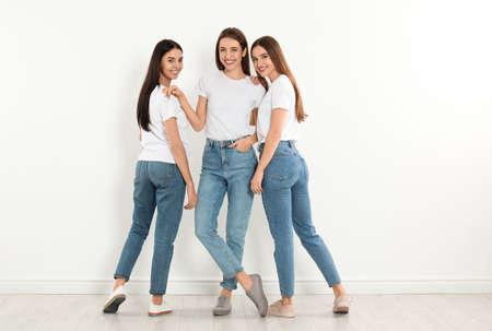 Groupe de jeunes femmes en jeans élégants près du mur blanc