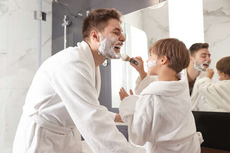 Dad and son with shaving foam on their faces having fun in bathroom Stock Photo