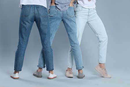 Grupo de mujeres jóvenes en jeans con estilo sobre fondo gris, primer plano