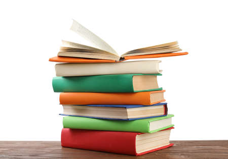 Stack of colorful books on wooden table against white background