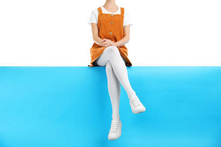 Woman wearing white tights and stylish shoes sitting on color background, closeup