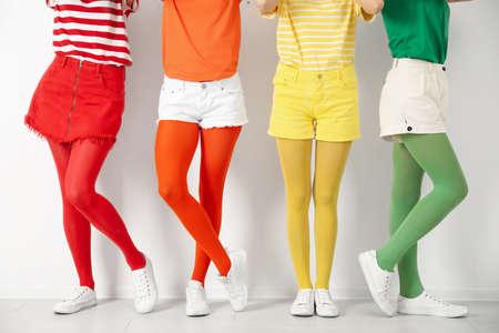 Women wearing bright tights near white wall, closeup