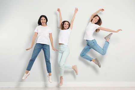 Grupo de mujeres jóvenes en jeans con estilo saltando cerca de la pared de luz Foto de archivo