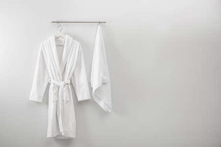 Kleiderbügel mit sauberem Bademantel und Handtuch an heller Wand. Platz für Text Standard-Bild