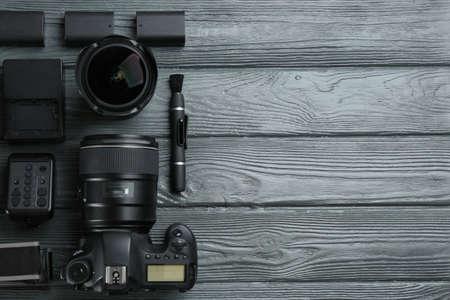 Flache Komposition mit Ausrüstung für professionelle Fotografen auf grauem Holztisch. Platz für Text