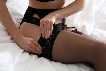 Young woman wearing stockings on bed at home, closeup Stock Photo