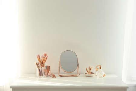 Piccolo specchio e prodotti per il trucco sulla toletta bianca all'interno
