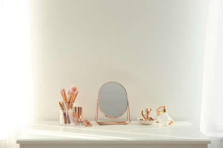 Small mirror and makeup products on white dressing table indoors