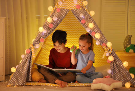 Little children with flashlight reading book in play tent at home Stock Photo - 137346827
